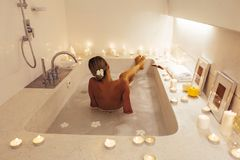Woman relaxing in bath with candles royalty free stock image