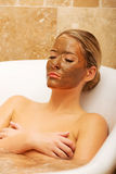 Woman relaxing in bath with chocolate mask on face Royalty Free Stock Photos