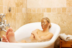 Woman relaxing in bath with chocolate mask on face Royalty Free Stock Photo