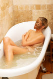 Woman relaxing in bath with chocolate mask on face Stock Photography