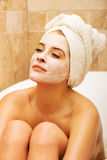 Woman relaxing in bath with face mask Royalty Free Stock Image