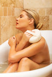 Woman relaxing in a bath and washing herself Stock Photography