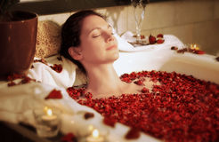 Woman relaxing in bathtub with rose blossoms Royalty Free Stock Photography