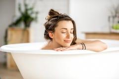 Woman relaxing in the bathtube. Beautiful young woman relaxing lying in the bathtube in the bathroom stock photo