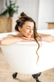 Woman relaxing in the bathtube. Beautiful young woman relaxing lying in the bathtube in the bathroom stock photography