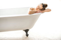 Woman relaxing in the bathtube. Beautiful young woman relaxing lying in the retro bathtube in the white bathroom royalty free stock photos