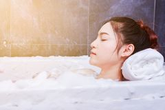 Woman relaxing in bathtube with eyes closed in bathroom. Woman relaxing in bathtube with eyes closed in the bathroom royalty free stock photography