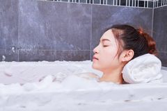Woman relaxing in bathtube with eyes closed in bathroom. Woman relaxing in bathtube with eyes closed in the bathroom stock images