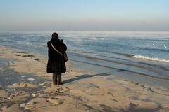 Woman relaxing on beach. Rear view of woman relaxing on beach in winter with Baltic sea in background Stock Images