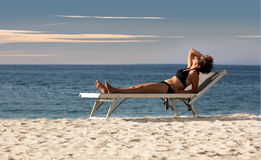 Woman relaxing on a beach. Looking at the sky Stock Photography