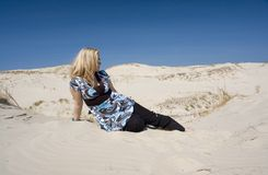 Woman Relaxing On Beach. Blond woman in short sleeved printed blouse and long black pants, lounging to her side alone on a sandy beach.  Head is turned in Stock Photos