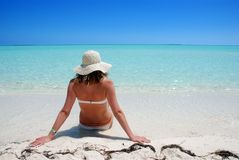 Woman relaxing on beach stock images