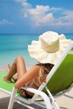 Woman relaxing on a beach Stock Photos