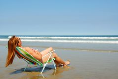 Woman relaxing on beach. Young woman relaxing in a beach chair on the ocean shore Stock Photography