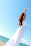 Woman relaxing at the beach with arms open. Enjoying her freedom wear long white dress Stock Images