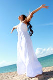 Woman relaxing at the beach with arms open enjoying her freedom. Wear long white dress Stock Images