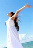 Woman relaxing at the beach with arms open enjoying her freedom. Wear long white dress Royalty Free Stock Photo