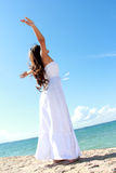 Woman relaxing at the beach with arms open enjoying her freedom. Wear long white dress Royalty Free Stock Image