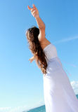 Woman relaxing at the beach with arms open enjoying her freedom. Wearing long white dress Stock Image