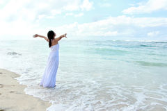 Woman relaxing at the beach with arms open. Woman wearing long white dress relaxing at the beach with arms open enjoying her freedom Stock Photos