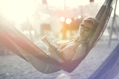 Woman relaxing on the beach. Beautiful young woman with book in her hand relaxing on the bich sunny day Stock Photo