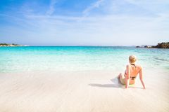 Woman relaxing on the beach. Caucasian blonde woman relaxing on the white  sandy beach enjoying the turquoise blue sea Royalty Free Stock Image