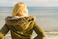 Woman relaxing on beach, cold day Royalty Free Stock Photo