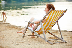 Woman relaxing on beach in deck chair Royalty Free Stock Photos