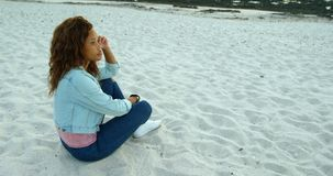 Woman relaxing on beach at dusk 4k. Thoughtful woman relaxing on beach at dusk 4k stock footage