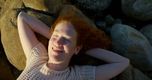 Woman relaxing on the beach at dusk 4k. Young woman relaxing on the beach at dusk 4k stock footage