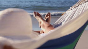 Woman relaxing on the beach in a hammock Royalty Free Stock Photo