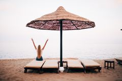Woman relaxing on beach lounge chair or sun deck with sea view on beach with raised hands. Concept of vacation beach and sea in su. Woman relaxing on beach royalty free stock photo