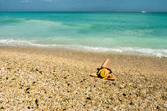 Woman relaxing on a beach made of stones Stock Photography