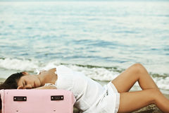 Woman relaxing on a beach with pink suitcase Stock Photos