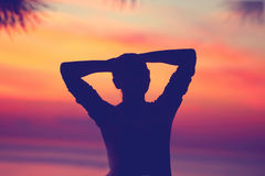 Woman relaxing on the beach. Silhouette of a young female with hands behind her head standing over beautiful sunset background, calmness and peace concept Stock Photos