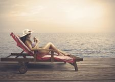 Woman relaxing on a beach. During sunset Royalty Free Stock Images