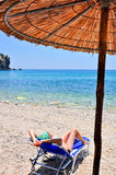 Woman relaxing at the beach. Under an umbrella in Greece Royalty Free Stock Photography