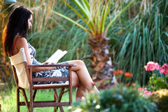 Woman is relaxing in a beautiful garden. Beautiful woman is relaxing in a beautiful garden and reading a book Royalty Free Stock Photography