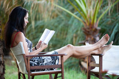 Woman is relaxing in a beautiful garden. Beautiful woman is relaxing in a beautiful garden and reading a book Royalty Free Stock Photo