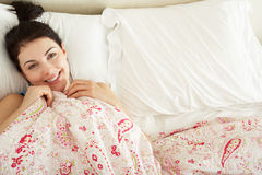 Woman Relaxing In Bed Stock Images