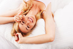 Woman relaxing in bed Stock Photos