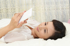 Woman relaxing in bed Royalty Free Stock Photography