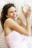 Woman Relaxing In Bed With Alarm Clock Stock Photography