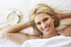 Woman Relaxing In Bed With Alarm Clock Royalty Free Stock Photo