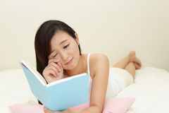 Woman relaxing in bed Royalty Free Stock Image