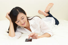 Woman relaxing in bed Stock Photography