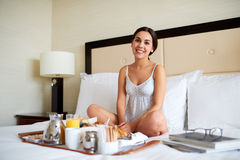 Woman relaxing in bed with breakfast tray. Stock Photos