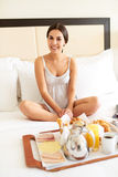 Woman relaxing in bed with breakfast tray. Stock Images