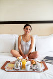 Woman relaxing in bed with breakfast tray. Royalty Free Stock Image