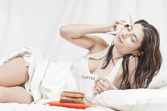 Woman relaxing on bed with a cake and a shell Stock Images